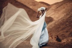 Free Black Bride Stands And Holds Waving Bridal Veil In Her Hands On Background Of Beautiful Landscape. Stock Image - 119503711