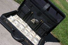 Black briefcase full of cash. A black briefcase full of cash, and a derringer pistol with extra shells. Lays askew on the ground. Could it be a Drug Deal gone royalty free stock photos