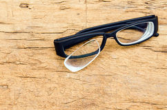 Black broken eyeglasses on wood background Stock Photography