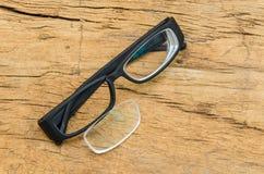 Black broken eyeglasses on wood background Stock Photos