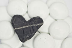 Black broken stoned hearth. And white rounded stones Stock Photos
