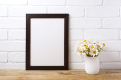 Black brown frame mockup with chamomile bouquet in rustic vase royalty free stock photos