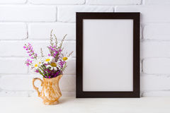 Black brown frame mockup with chamomile and purple flowers in g royalty free stock images