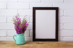 Black brown  frame mockup with maroon purple flowers in mint pit. Black brown  frame mockup with maroon purple field flowers in polka dot mint green pitcher vase Stock Image