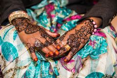 Black and Brown Henna Hands Drawings on Women for African Wedding Ceremony with Big Rings. stock photo