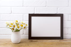 Black brown  landscape frame mockup with chamomile bouquet in ru Stock Photos