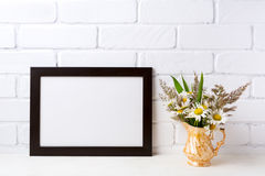 Black brown  landscape frame mockup with chamomile and grass in royalty free stock photography