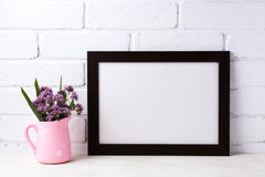 Black brown landscape frame mockup with purple flowers in pink stock photo