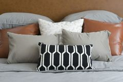 Pillows setting on bed with brown leather headboard Royalty Free Stock Images