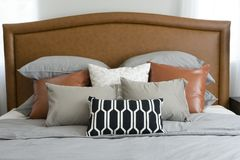 Pillows setting on bed with brown leather headboard Stock Photography