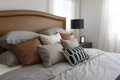 Pillows setting on bed with brown leather headboard Stock Image