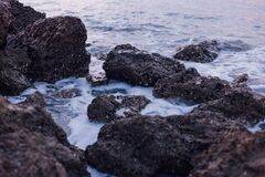 Black and Brown Rocks on Sea during Daylight Stock Photography