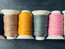 Black, brown, yellow, grey, pink and white thread rolls on a woo Stock Photography