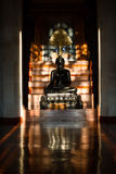 Black buddha in the dark room Royalty Free Stock Image