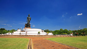 Black Buddha statue with garden against blue sky Stock Photos
