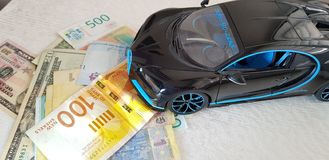 Black Bugatti Chiron metal toy standing with front wheels on paper money of various countries stock photo