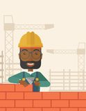 Black builder man is building a brick wall Royalty Free Stock Image