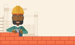 Black builder man is building a brick wall Stock Images