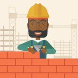 Black builder man is building a brick wall Royalty Free Stock Photography