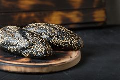 Black bun with sesame on the table. Black loaves with sesame on the table royalty free stock photo