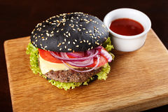 Black burger on the board. With fried potatoes; cutlet; vegetables and cheese; with sauce on a wooden board stock photography