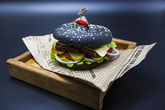 Black burger. A burger with a black roll slices of juicy marble beef, fused cheese, fresh salad and sauce of a barbecue. A burger Royalty Free Stock Images