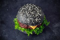 Black Burger with Cheese, Beef and Green salad leaves. Homemade cheeseburger Royalty Free Stock Photo
