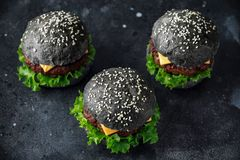 Black Burger with Cheese, Beef and Green salad leaves. Homemade cheeseburger Stock Photography
