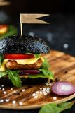 Black burger with cutlet, greens, cheese, onions and tomatoes on a wooden plate on a dark table stock photos