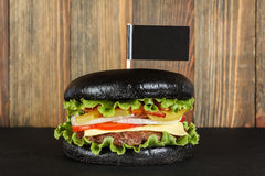 Black burger with flag on wood background Royalty Free Stock Images