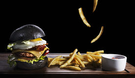 Black burger and french fries isolated on black. Hamburger with fried egg and french fries on wooden board isolated on black background stock images
