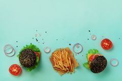 Black burger, french fries potatoes, tomatoes, cheese, onion, cucumber and lettuce on blue background. Top view. Fast food banner. With copy space. Take away stock images