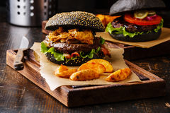 Black burger with meat, onion rings fries and potato wedges Stock Photos