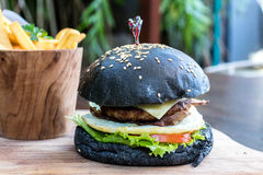 Black burger with meat patty, cheese, tomatoes, mayonnaise, french fries in a wooden plate. Modern fast food lunch. Black burger with meat patty, cheese Stock Photography