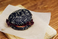 Black burger. serving cheeseburger or hamburger with salad on wo. Oden desk. catering in food court at mall concept. space for text. modern kitchen Stock Photography
