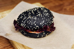 Black burger. serving cheeseburger or hamburger with salad on wo. Oden desk. catering in food court at mall concept. space for text. modern kitchen Stock Photos