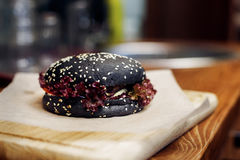 Black burger. serving cheeseburger or hamburger with salad on wo. Oden desk. catering in food court at mall concept. space for text. modern kitchen Stock Photo