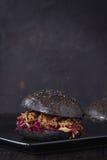 Black burger with stews Royalty Free Stock Photo