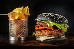 Black Burger with two patties on a black background with French stock image