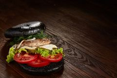 Black burger on vintage wooden background, top view, close-up, selective focus, copy space. Black burger on vintage wooden background, top view, close-up Royalty Free Stock Image
