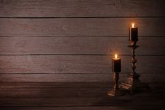 Black burning candles in candlesticks on old wooden background. The black burning candles in candlesticks on old wooden background stock image