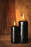 Black burning candles on wooden background Stock Image