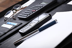 Black business briefcase open wide. Skewed view of opened black briefcase with various office, computing and communication stuff inside Stock Image