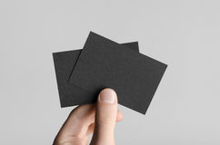 Black Business Card Mock-Up (85x55mm). Male hands holding black cards on a gray background Stock Images