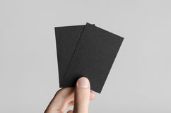 Black Business Card Mock-Up (85x55mm). Male hands holding black cards on a gray background Stock Image