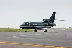 Black business jet taxiing from the runway Stock Image