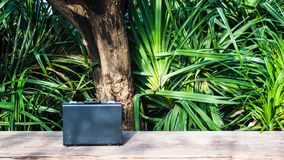 Black business leather briefcase on wooden surface with green nature background. Black business leather briefcase, handbag with key lock at office, on wooden stock photos