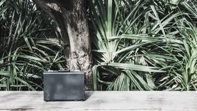 Black business leather briefcase on wooden surface with green nature background. Black business leather briefcase, handbag with key lock at office, on wooden stock image