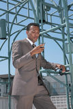 Black Business Man in a Suit Looking At Cell Phone Royalty Free Stock Image