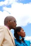 Black business people. Outdoor profiles portrait of two African American black business people, a woman and a man, staring into the future in front of blue sky Royalty Free Stock Photography